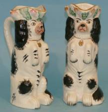 A Pair of Reproduction Staffordshire Jugs inform of Seated Spaniels on white and black ground  with vine decoration 25