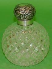 A Victorian Round Bulbous Cut Glass Scent Bottle having tooth cut decoration, having silver neck and hinge lid with embossed floral and scroll decoration (hinge in need of restoration) Birmingham 1898, 13cm high